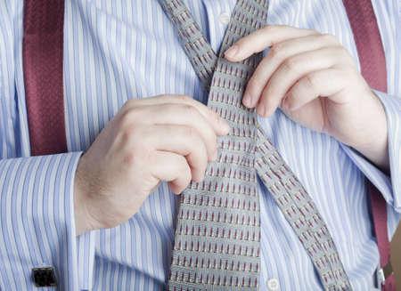 A man in business attire tying his necktie Stock Photo - 8561339