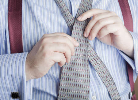 A man in business attire tying his necktie