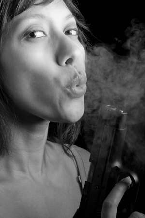 ethnic woman blowing smoke from the barrel of a handgun Stock Photo - 8628371
