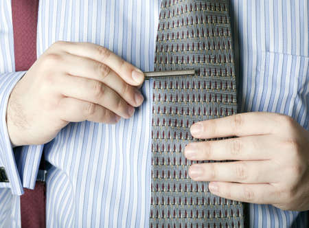 Businessman attaching a tie bar to his necktie