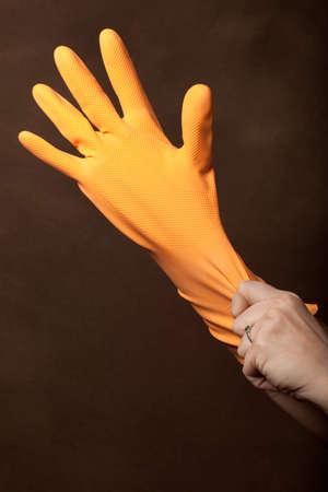 woman pulling on an orange dishwashing glove