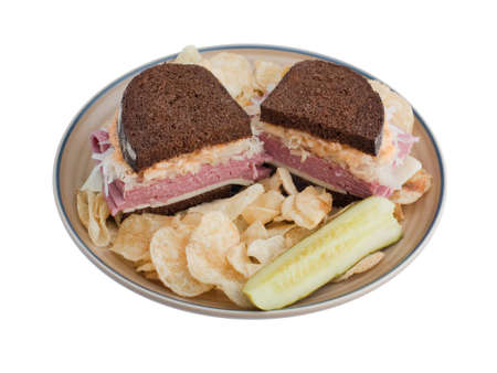 reuben: Reuben sandwich on a plate with pickle and potato chips