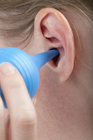 woman cleaning her ear with a bulb syringe