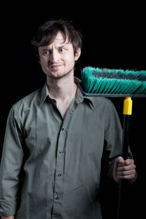 janitor with broom frowning