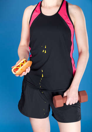 A woman with a dumbbell and a hotdog. Illustrates concept of unhealthy diet and excercise. Humousouly, this woman has dripped mustard on her shirt. Photographed with studio lighting in front of a blue backdrop.
