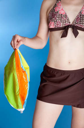 A woman in a two-piece swimsuit holds an uninflated (deflated) beach ball. Photographed with studio lights in front of a blue backdrop. Stock Photo