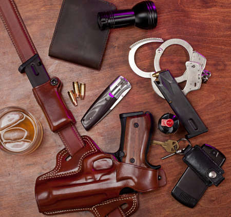Equipment typically carried by a law enforcement officer, on a wooden table with a glass of whiskey.