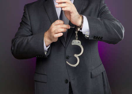 Businessman is using a key to unlock a pair of handcuffs. Image can be used metaphorically to represent business concepts about removing restrictions.
