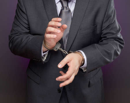 A man in a suit and tie wearing handcuffs
