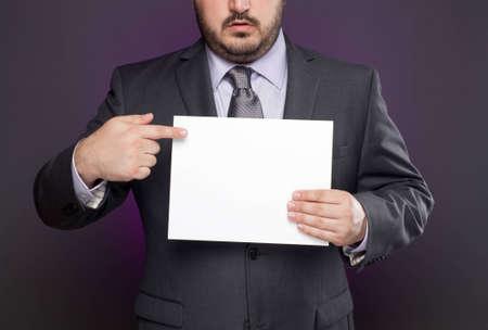 Un empresario con traje gris y corbata morada y camisa p�rpura utiliza su dedo para se�alar una arroba en blanco que est� sosteniendo. Fondo p�rpura se logra con luz de color studio, no un efecto de software. Foto de archivo - 9883326