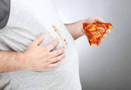 slob: an overweight man holds a slice of pizza with a missing bite. he has pizza sauce on his hands and is wiping it on his shirt. photographed with studio light in front of a gray backdrop. Stock Photo