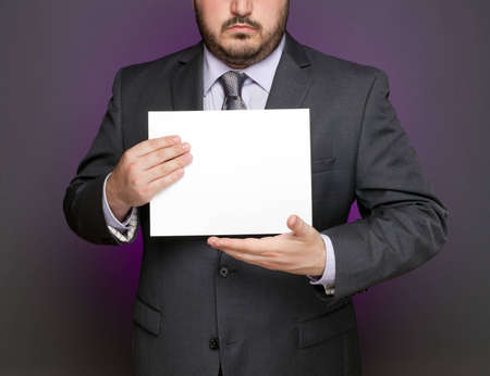 A businessman presents a blank document.