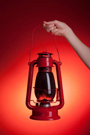 A woman holds up a sooty kerosene lantern. Red backdrop with orange spotlight gives the impression of light emanating from the lantern.  Stock Photo