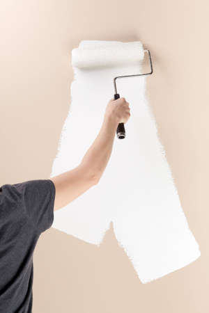 Woman using roller to paint a beige wall white.  Stock Photo