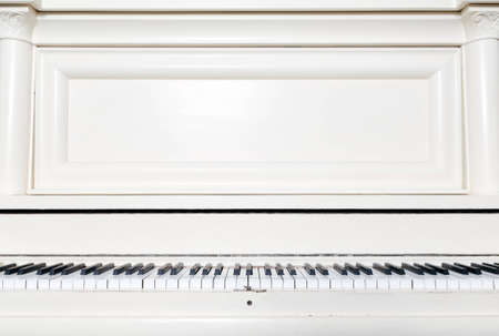 A white upright piano, seen from the perspective of the player.