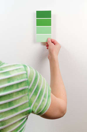 A woman holds a paint swatch card near a wall to compare the green shades.