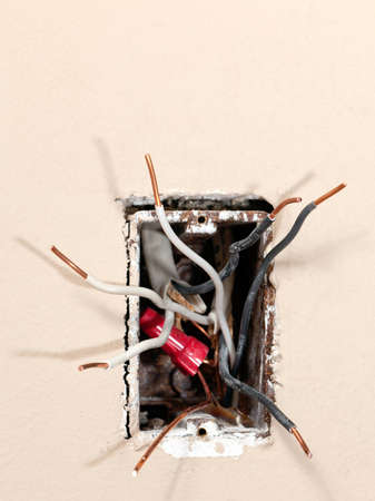Several exposed copper wires protruding from a beige wall.