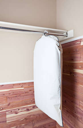 Several garments in a garment bag, hanging in a cedar lined closet. Stock Photo