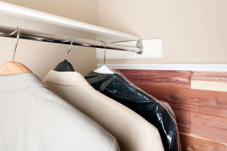 Three mens suits on hangers in a cedar lined closet. Stock Photo