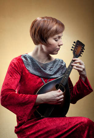 A woman wearing a red velvet tunic strums a mandolin.