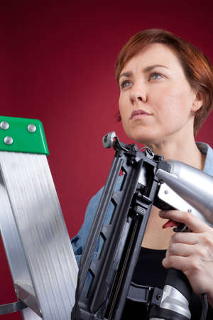 A woman stands on an aluminum ladder and holds a nail gun, ready to do a construction project.