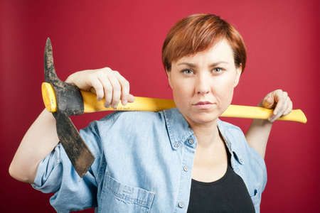 A red haired woman wearing a denim shirt holds a pickaxe over her shoulders.