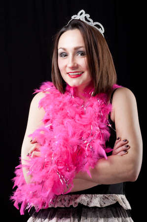 A happy young woman dressed for a bachelorette party in a short dress, pink feather boa, and plastic tiara.