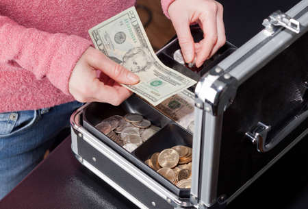 A woman making change for a twenty  dollar bill with coins from a cashbox.
