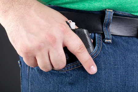 A man draws a small concealed handgun out of his pocket Stock Photo