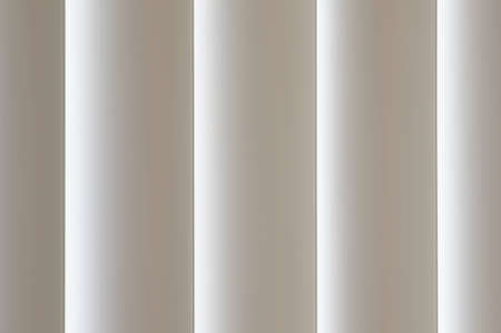 Closed Vertical blinds, with light leaking through. Abstract background texture. Stock Photo