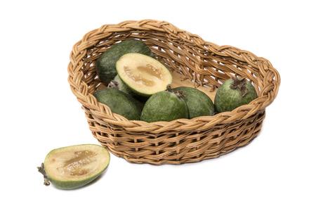 meaty: Ripe feijoa fruit in the wicker basket on a white background