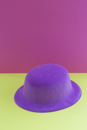 Still-life with purple hat on a colored background Фото со стока