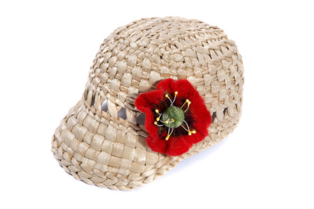 Cap made of straw with a flower from a felted wool on a white background Stock Photo