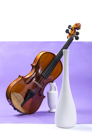 Still life with violin and white vases violet background Stock Photo