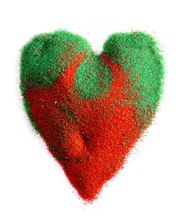 particulate: Symbol of heart in the sand of red and green on a white background