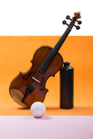 Still-life with a violin, a ball and a dark bottle Stock Photo