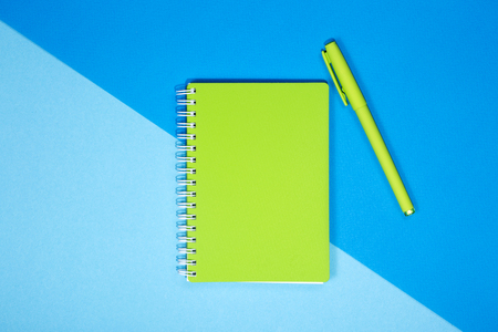 Green notebook and pen on a colored background