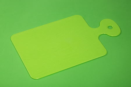 Plastic cutting board in green on a green background