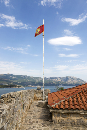 Flag of Montenegro on the flagpole of the observation platform of the ancient fortress Citadel. The city of Budva.