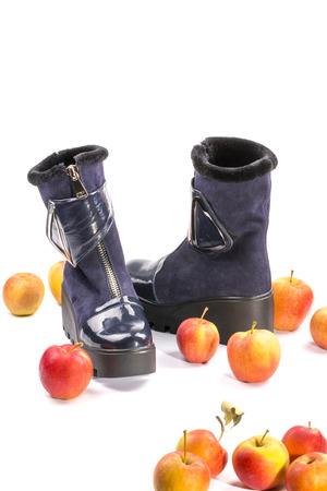 Womens winter boots on high soles among ripe apples