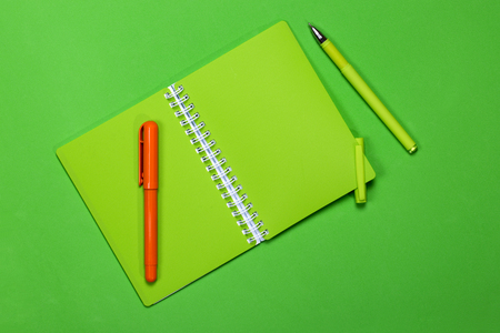 ball pens stationery: Green notebook and two pens on a color background Foto de archivo