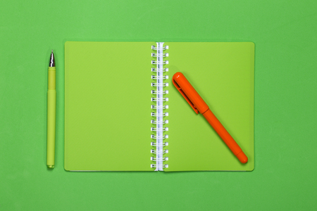 Green notebook and two pens on a color background Stock Photo