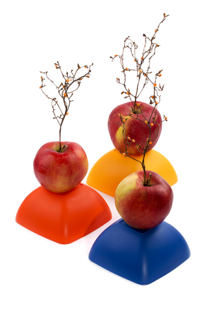 Three ripe red apples with a plant similar to a tree on a yellow, red and blue figure Фото со стока