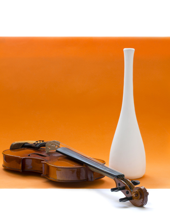Still life with violin and white vase on an orange background