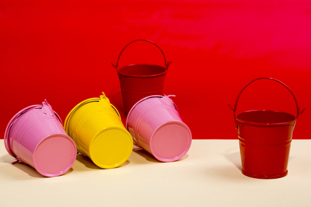 Pink, red and yellow buckets on a colored background