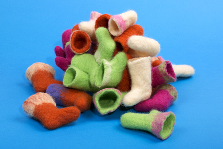 Heap of souvenir boots made of felted wool on a blue background Stock Photo