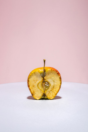 Old apple in a cut on a colored background Banco de Imagens