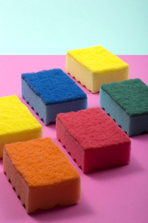 Multi-colored kitchen sponges on a colored background