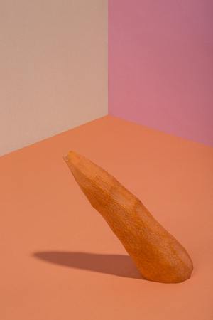 Abstract still life with a peeled carrot on a colored background Stock Photo