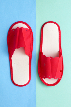 Red one-off slippers for hotel on a colored background